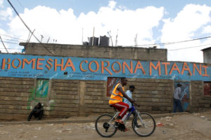 A man cycles past a wall mural advocating against the coronavirus disease (COVID-19) outbreak in Nairobi